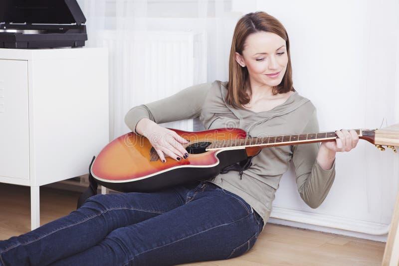 Маленькая девочка на софе играя гитару стоковое фото