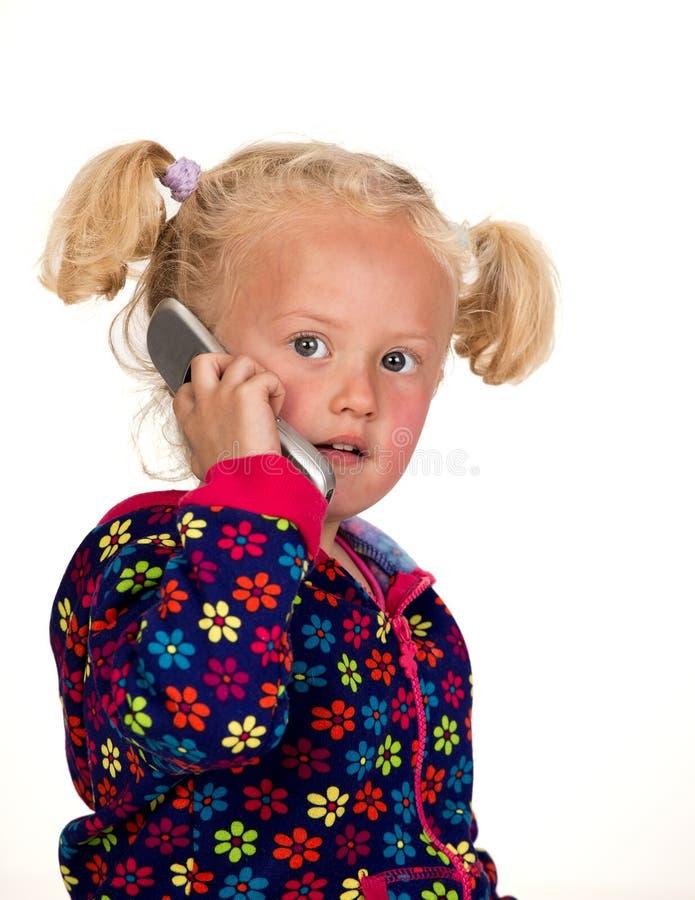 Маленькая девочка на телефоне стоковое изображение rf
