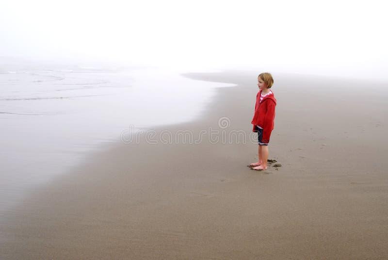 Маленькая девочка на туманном пляже нося красную куртку стоковая фотография rf