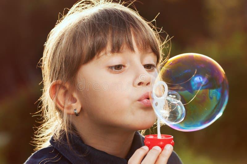 Маленькая девочка надувает большой пузырь стоковые изображения