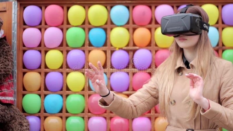 Маленькая девочка на улице в бежевом пальто играя имеющ стекла шлемофона виртуальной реальности vr потехи нося, красочную предпос видеоматериал