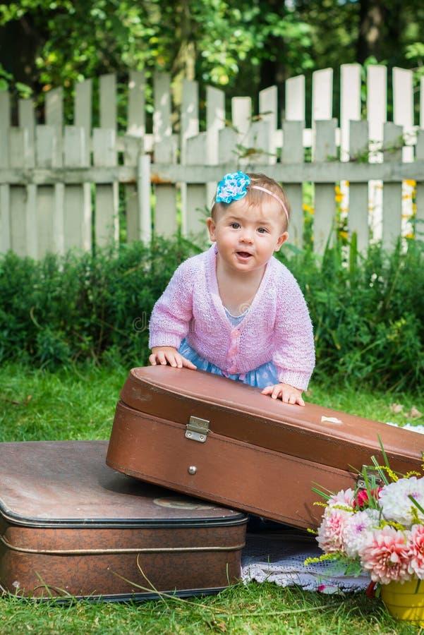 Маленькая девочка на чемодане стоковая фотография rf