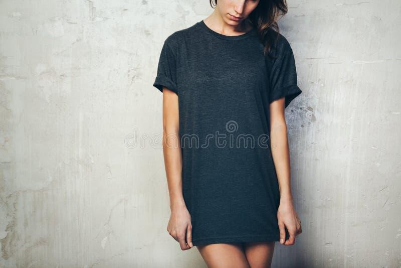 Маленькая девочка нося пустую черную футболку стена пятна предпосылки конкретная светлая средняя горизонтально стоковые изображения