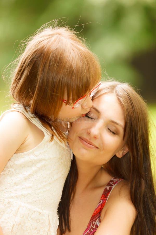 Маленькая девочка обнимая его мать выражая нежные чувства Любовь стоковые фотографии rf