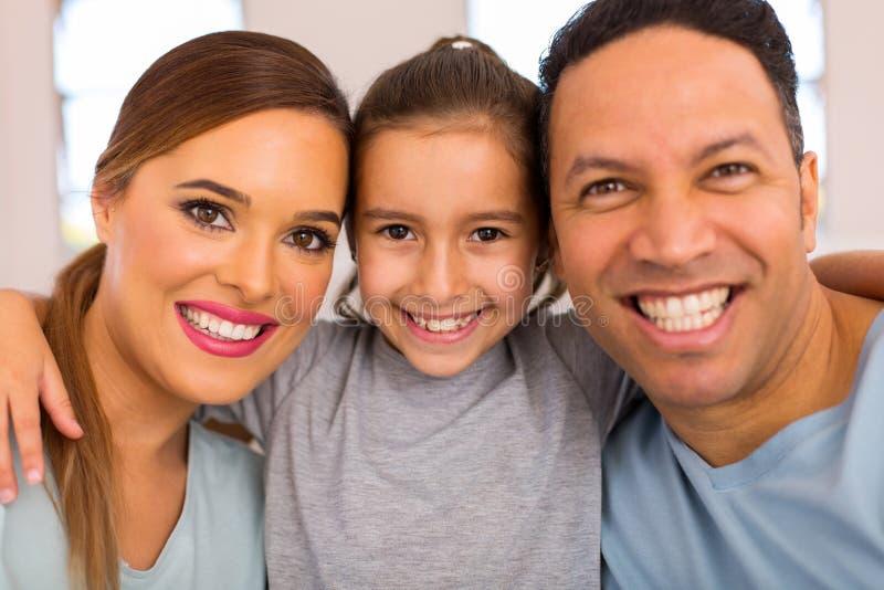 Маленькая девочка обнимая родителей стоковая фотография