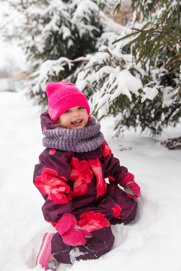 Маленькая девочка около зеленого дерева стоковое фото rf