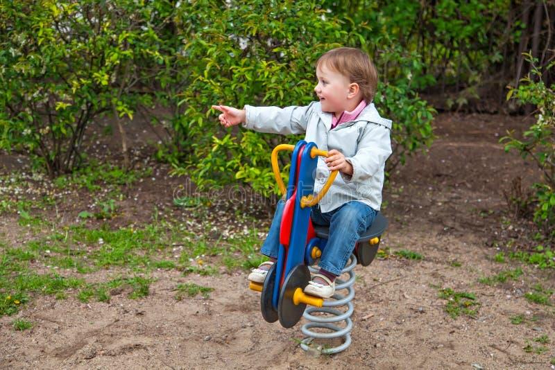 Маленькая девочка освобождая качание весны стоковая фотография rf