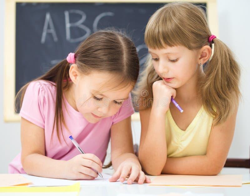 Маленькая девочка пишет используя ручку стоковые изображения rf