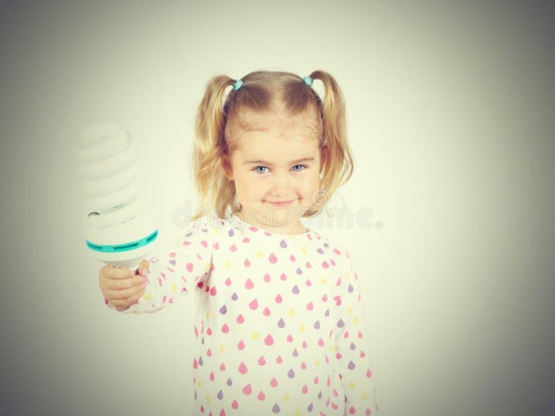 Маленькая девочка показывает большие энергосберегающие электрические лампочки стоковые изображения rf