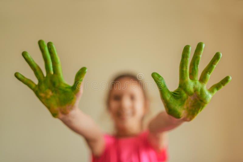 Маленькая девочка показывает руки которые покрасили зеленую краску стоковое изображение rf