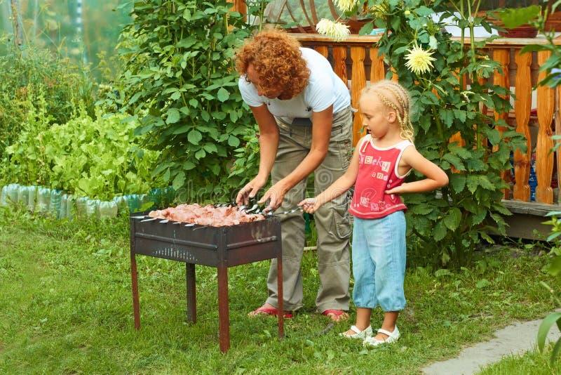 Маленькая девочка помогая ее матери сварить shish kebab стоковое фото rf