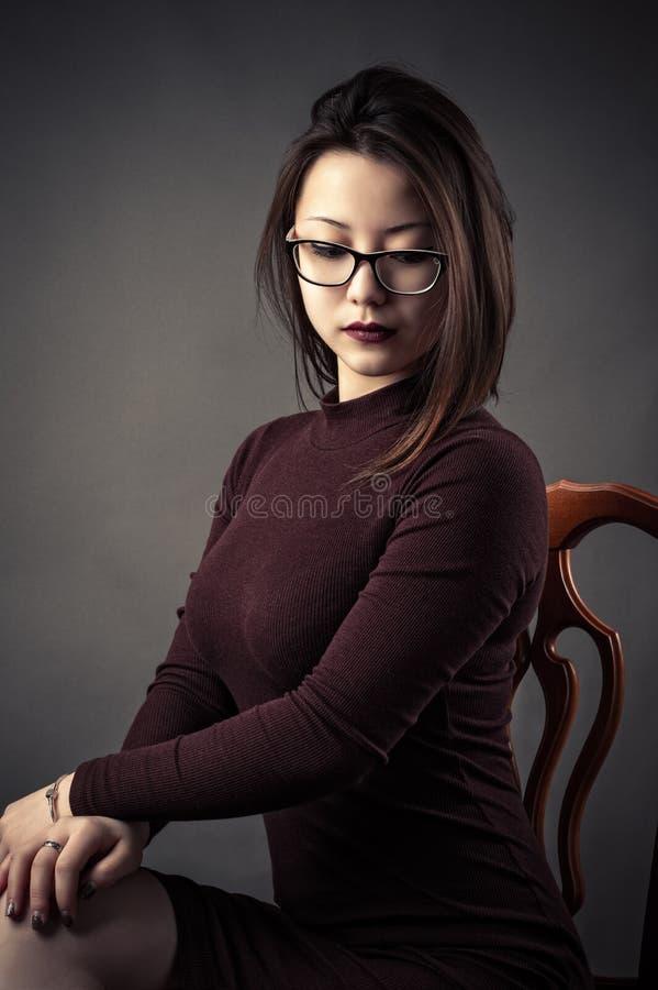 Маленькая девочка портрета задумчивая сидя на стуле стоковые изображения rf