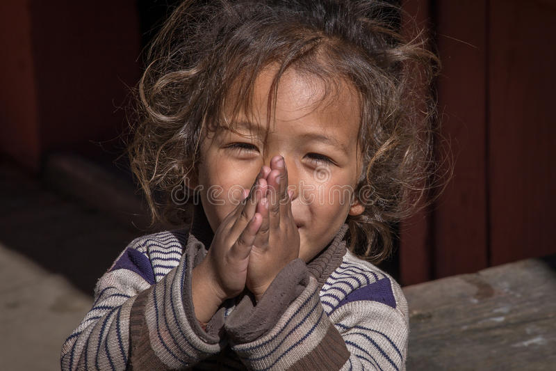 Маленькая девочка портрета с сложенными руками в улице, Непале конец вверх стоковая фотография
