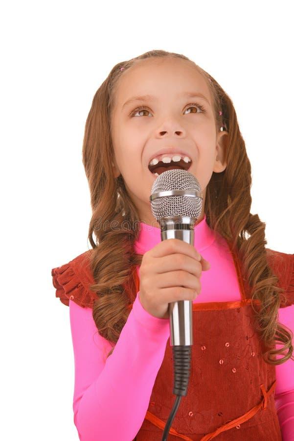 Маленькая девочка поя в микрофон стоковые изображения rf