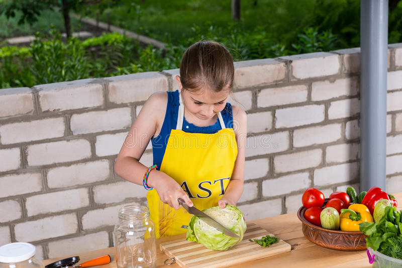Маленькая девочка подготавливая свежую капусту стоковое фото