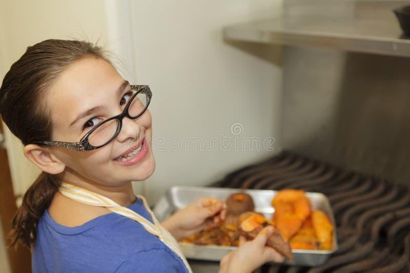 Маленькая девочка подготавливая сладкие картофели стоковая фотография rf