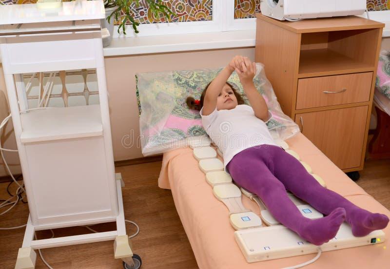 Маленькая девочка получает процедуру magnetotherapy Physioth стоковое фото