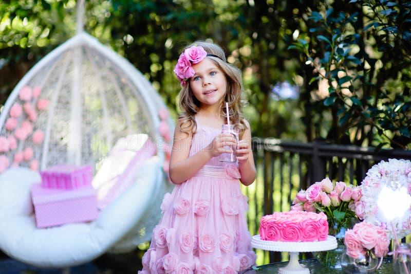 Маленькая девочка празднует с днем рождения партию с розой внешней стоковое изображение
