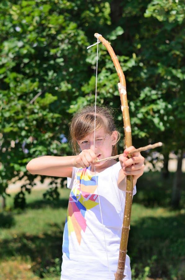 Маленькая девочка практикуя с луком и стрелы стоковое фото rf