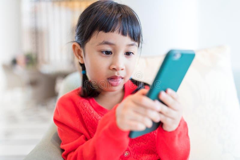 Маленькая девочка пристрастившийся к использованию мобильного телефона стоковое фото