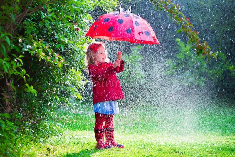 Маленькая девочка при зонтик играя в дожде стоковое изображение