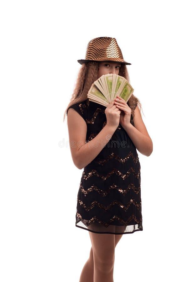 Маленькая девочка при длинные волосы нося черную шляпу платья и золота с микрофоном в его руке и деньгах на белой предпосылке в с стоковое фото