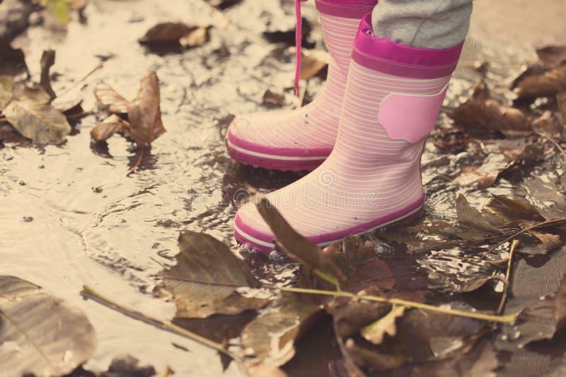 Маленькая девочка при розовые резиновые ботинки стоя в лужице стоковые изображения