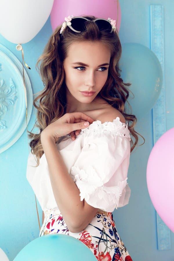 Маленькая девочка при темное вьющиеся волосы и нежный состав, представляя с красочными воздушными шарами стоковое фото