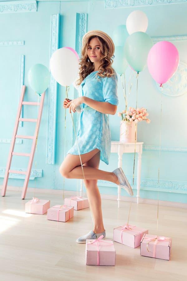 Маленькая девочка при темное вьющиеся волосы и нежный состав, представляя с красочными воздушными шарами стоковые изображения