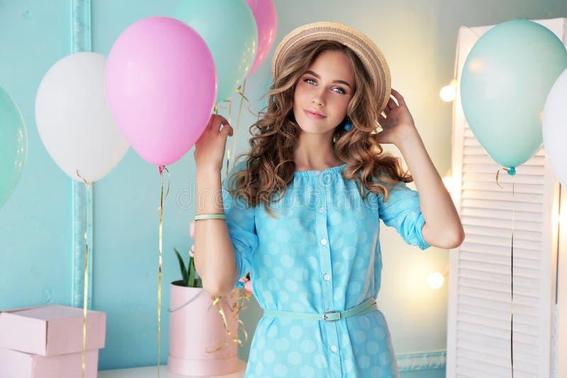 Маленькая девочка при темное вьющиеся волосы и нежный состав, представляя с красочными воздушными шарами стоковое фото rf