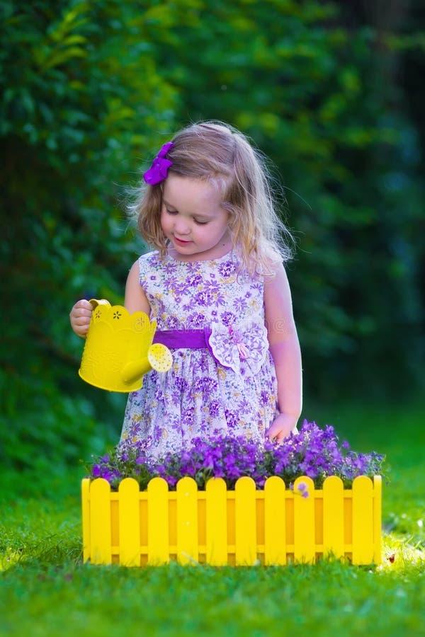 Маленькая девочка работая в цветках сада моча стоковые изображения rf