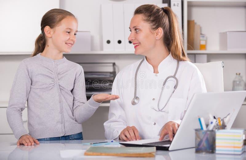 Маленькая девочка разговаривая с доктором около больным горла стоковая фотография rf