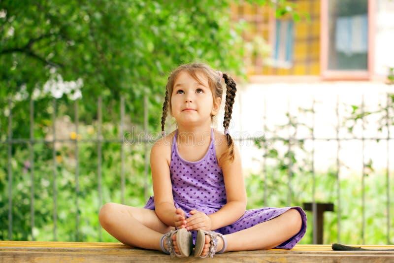 Маленькая девочка размышляя outdoors. Релаксация стоковые изображения rf