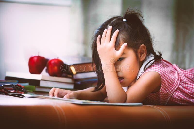 Маленькая девочка ребенка азиатская пробурена для того чтобы прочитать книгу стоковые изображения rf