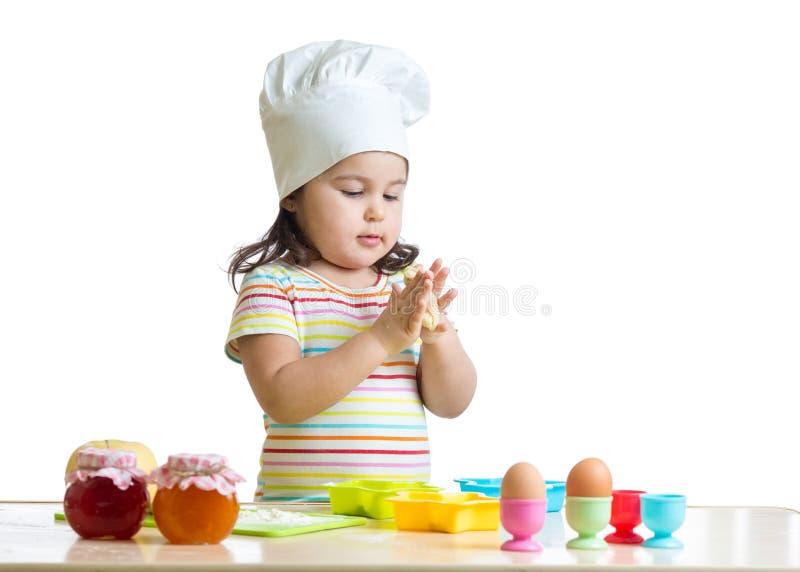 Маленькая девочка ребенка замешивая тесто для печений, изолированное на белизне стоковое фото