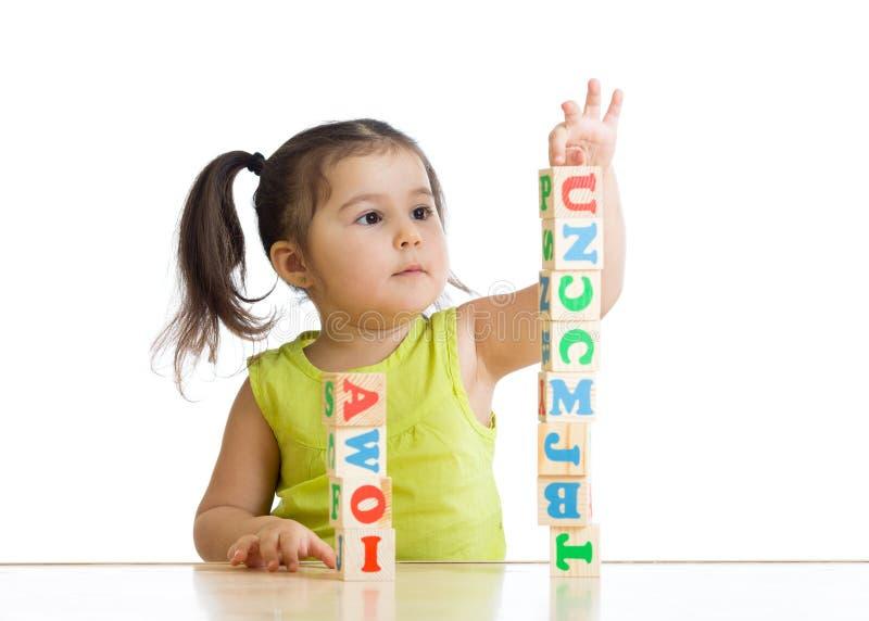Маленькая девочка ребенка играя деревянные игрушки стоковая фотография