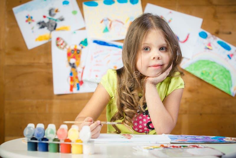 Маленькая девочка рисует в красках альбома пестротканых стоковое изображение rf