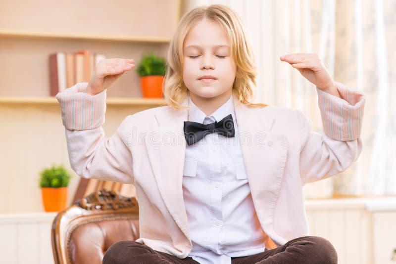 Маленькая девочка сидит положив ногу на ногу на столе стоковое изображение rf