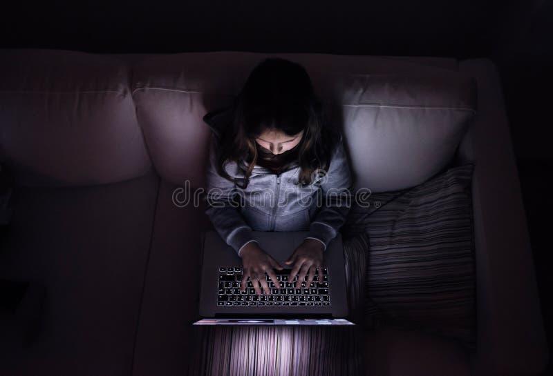 Маленькая девочка, сидящ в темной, играющ с компьтер-книжкой стоковое изображение
