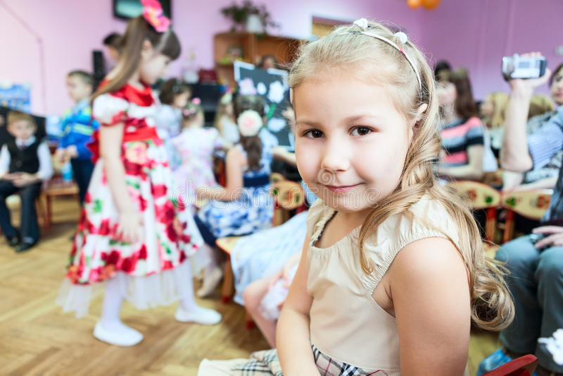 Маленькая девочка сидя в комнате класса детского сада на уроке музыки стоковая фотография