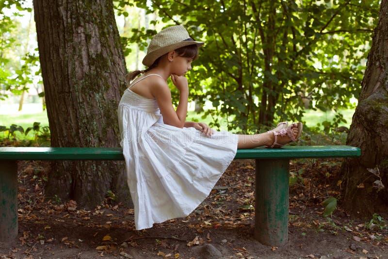 Маленькая девочка сидя в мысли стоковая фотография