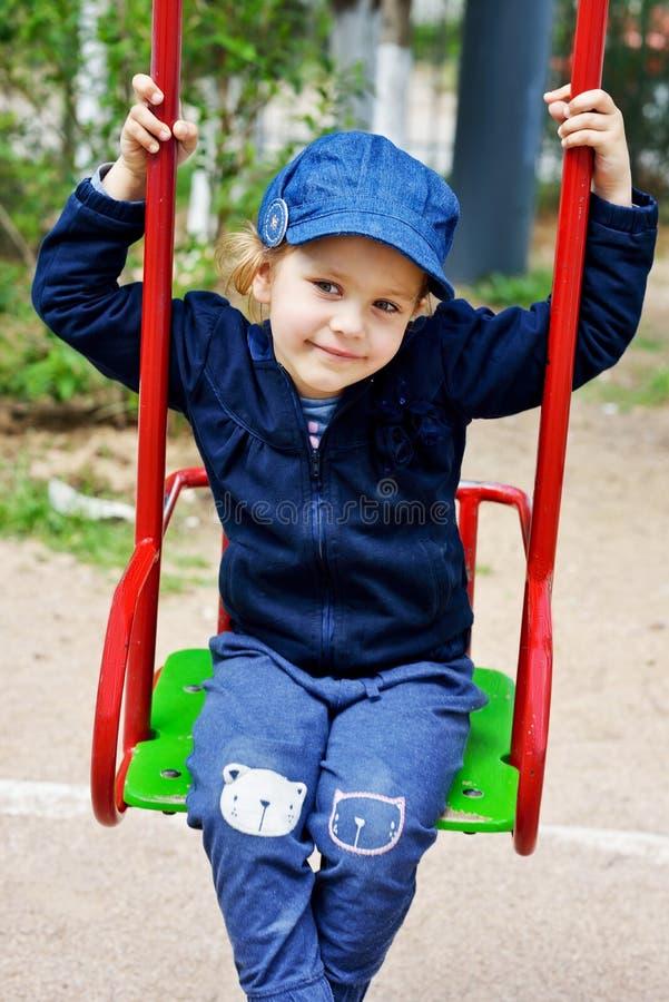 Маленькая девочка сидя на качании стоковое изображение rf