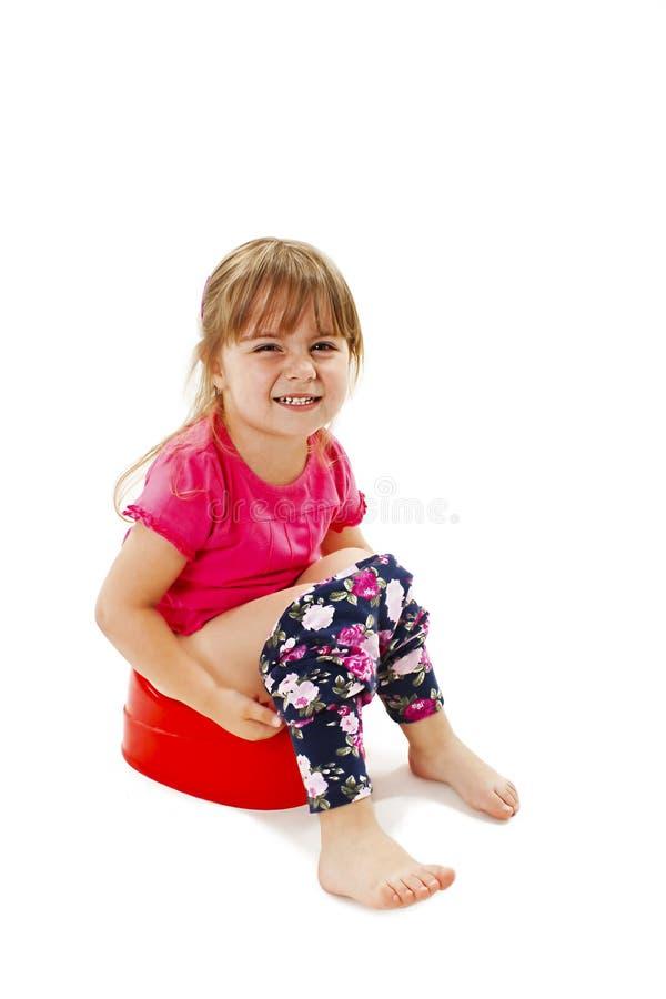 Маленькая девочка сидя на ночном горшке стоковая фотография