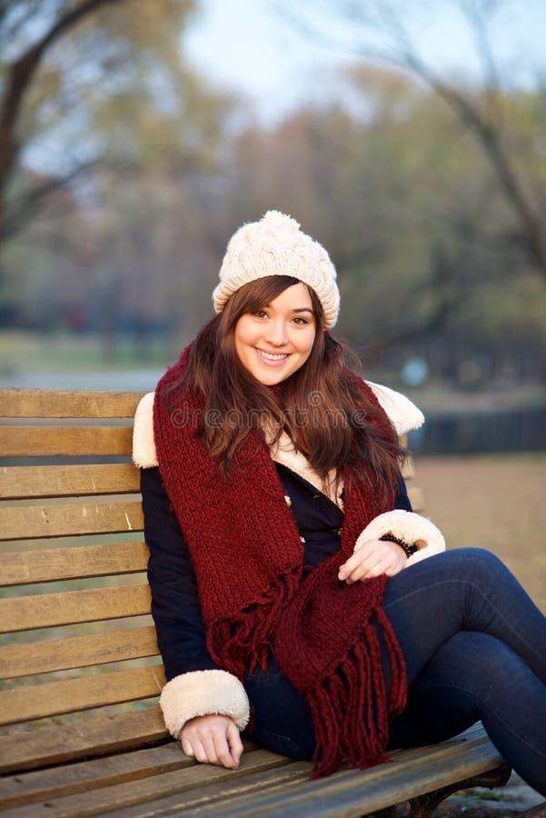 Маленькая девочка сидя на стенде в парке стоковые фотографии rf