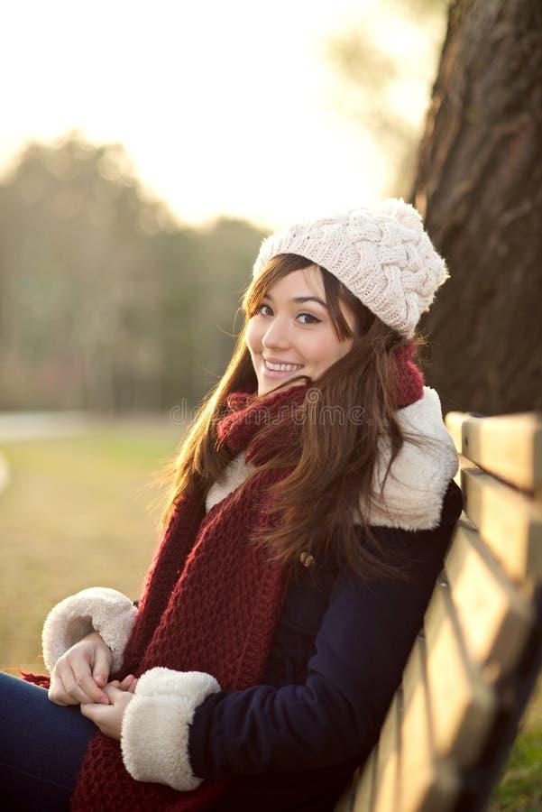 Маленькая девочка сидя на стенде в парке стоковые фото