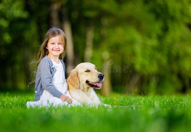 Маленькая девочка сидя на траве с retriever labrador стоковое фото