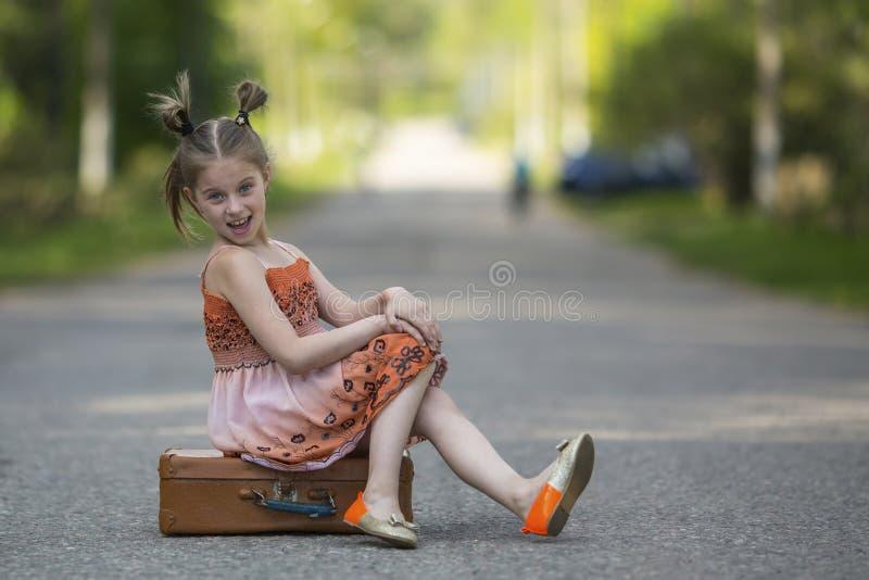 Маленькая девочка сидя на чемодане на дороге стоковое изображение rf