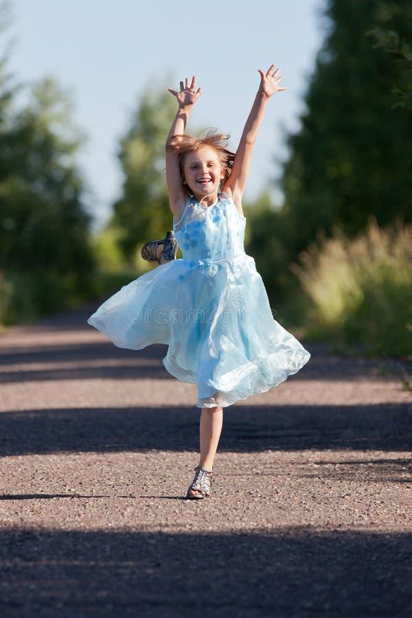 Маленькая девочка скача и радуясь стоковая фотография rf