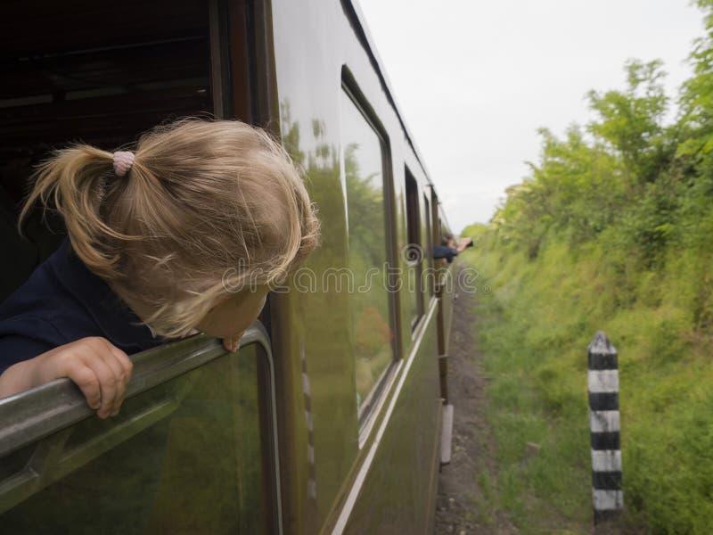 Маленькая девочка смотрит из окна стоковые фото
