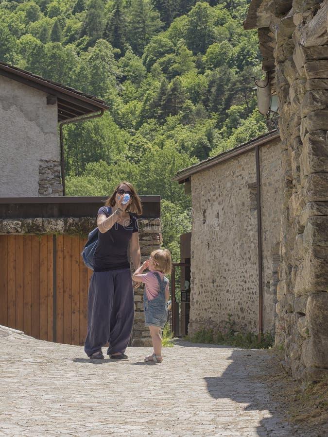 Маленькая девочка смотрит мать выпивая на бутылке стоковая фотография rf